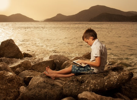 Child on the beach with tablet computer photo