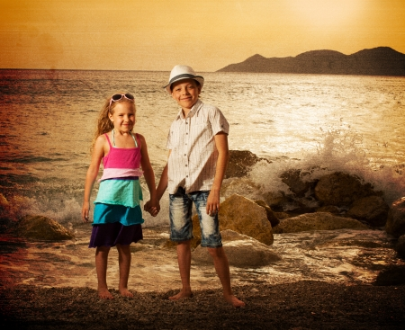 Children on the sea at sunset. Kids vacations. photo