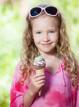 Happy little girl with ice cream outdoors photo