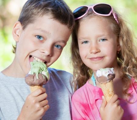 Gelukkige kinderen met ijs buitenshuis Stockfoto