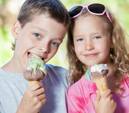 face cream: Happy children with ice cream outdoors Stock Photo