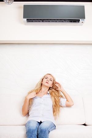 航空ショー: リモート コントロール、エアコンを家庭で保持している女性。ソファの上の幸せな女