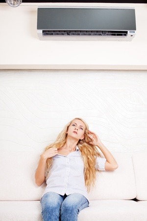 hands in the air: Woman holding a remote control air conditioner at home. Happy woman on sofa Stock Photo