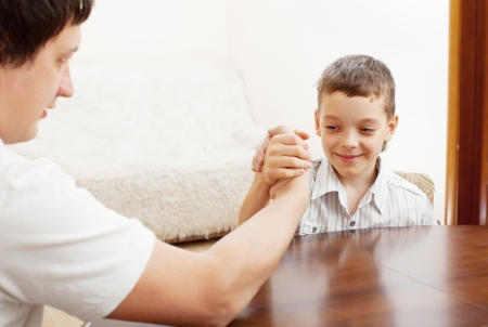 Father and son arm wrestling. Dad play with child photo