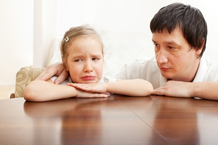 sorry: Father comforts a sad girl. Problems in the family