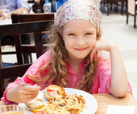 Child eating pasta in cafe. Little girl eating spaghetti. Food photo