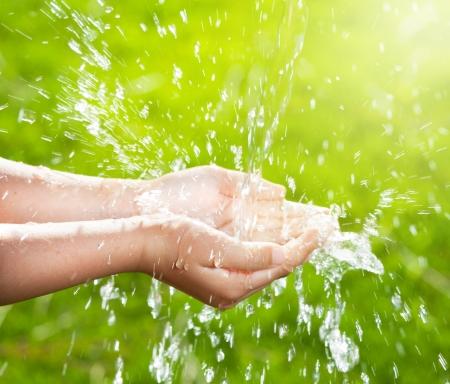 子供たちの手に注ぐ水のストリーム。 写真素材