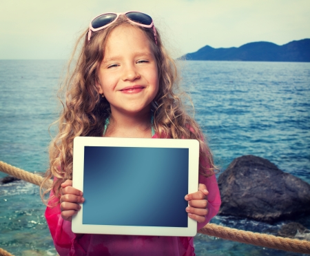 Ni�o en la playa con la computadora tablet. Muchacha que muestra la pantalla digital de la PC photo