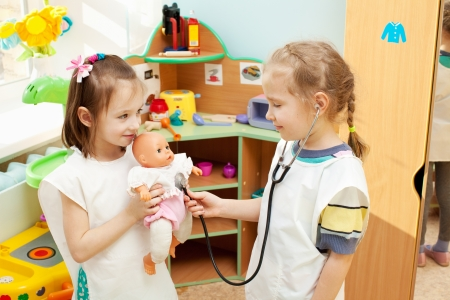 doctor toys: Child in kindergarten. Kids in nursery school. Girl playing with doll at infant school Stock Photo