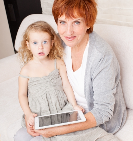 Family wiht tablet computer at sofa. Grandmother and little girl at home on sofa photo