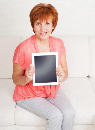 Mature woman with tablet pc. Female showing screen  photo