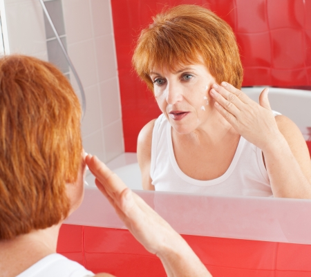dermatology: Mature woman gets cream on face in bathroom. Adult female looking at mirror Stock Photo