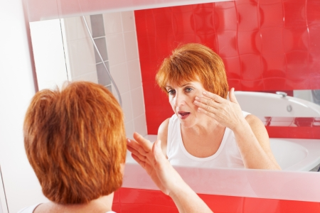 Mature woman gets cream on face in bathroom. Adult female looking at mirror Stock Photo - 20706710