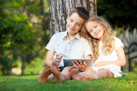 Children with tablet computer outdoors. Girl and boy playing at pc  photo