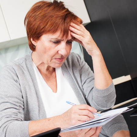 Sad businesswoman with document. Elderly woman writing a letter photo