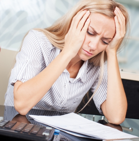 finance problems: Sad businesswoman looks at the documents. Female working Stock Photo