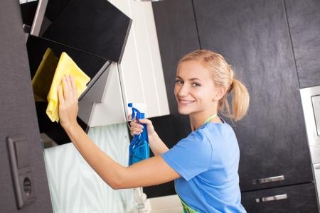 Frau Reinigung Küche. Junge Frau wäscht Dunstabzugshaube