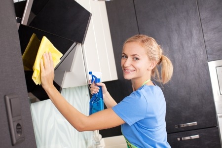 sprays: Woman cleaning kitchen. Young woman washing kitchen hood