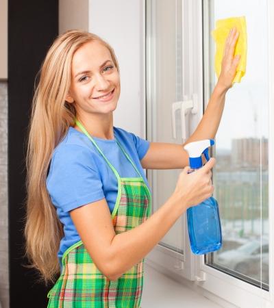 sirvienta: Ventana de lava de la mujer. Ama de casa de limpieza de ventanas en casa. Las tareas del hogar