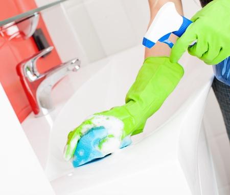 manos limpias: Mujer que limpia el fregadero y grifo en el ba�o en el hogar