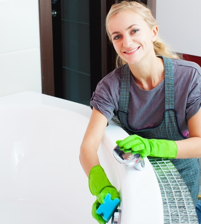silver service: Woman cleaning bath at home. Female washing bath Stock Photo