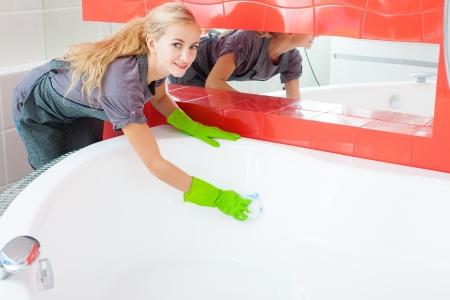disinfecting: Woman cleaning bath at home. Female washing bathtub. Tub