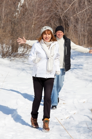 Happy seniors couple in winter park. Elderly mature people photo