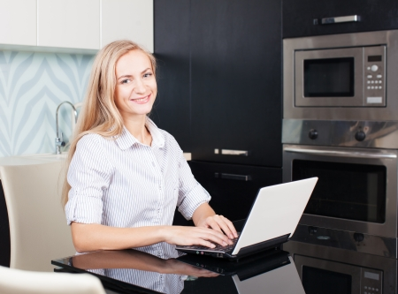 Female with computer. Woman working on laptop at home photo