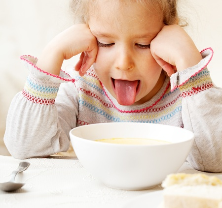 angry child: Child looks with disgust for food.  Stock Photo