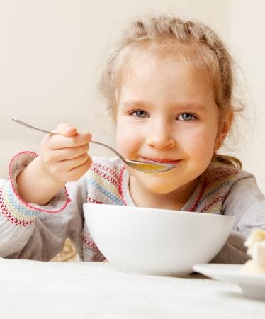Kind essen Suppe zu Hause. Kleines M?dchen haben ein Abendessen Standard-Bild