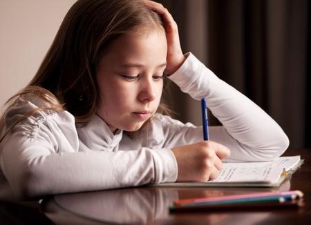 Child doing homework  Sad girl writing, reeding