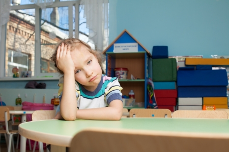 Sad child in kindergarten. Depression girl in nursery school
