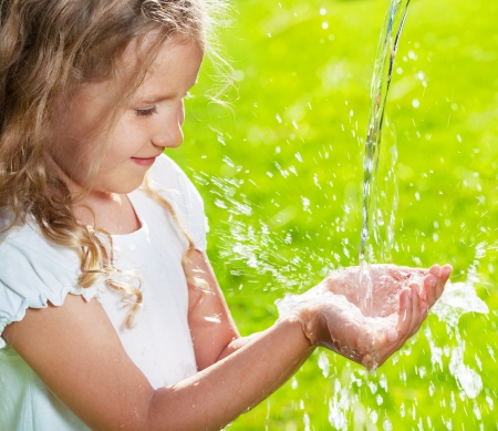 atrapar: Corriente de agua potable que vierte en las manos de los ni�os. Juego de ni�os con agua