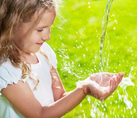 Stroom van schoon water gieten in de handen van kinderen. Kind spelen met water