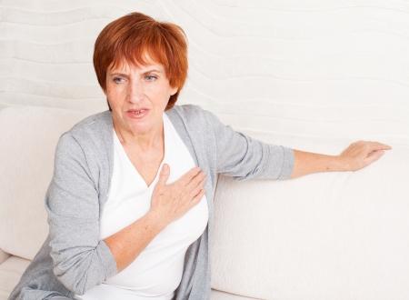 심장 통증. 성숙한 여자가 그녀의 마음을 보유하고있다 스톡 콘텐츠