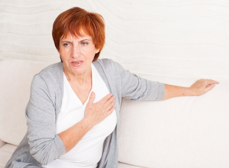 woman chest: Cardiac pain. Mature woman holds her heart