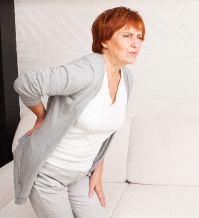 Adult woman has a backache. Mature female has pain in back Stock Photo