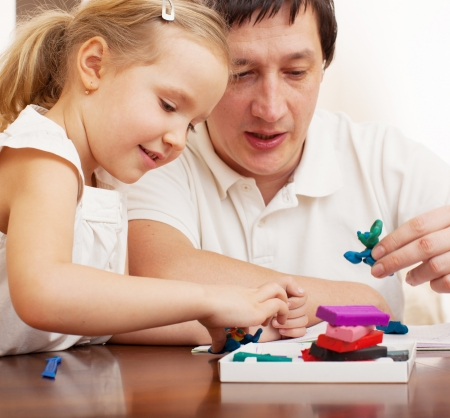 molded: Family molded from clay toys. Father play with girl at home