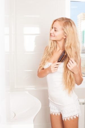 Woman combing in bathroom. Female with hairbrush photo