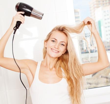 secador de pelo: Mujer secador de pelo cabello seco en el baño. Mujer con el secador en casa