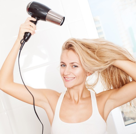 hair tied: Woman dry hair hairdryer at bathroom. Female with dryer at home