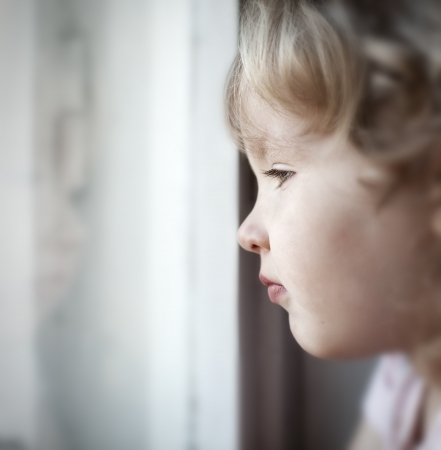 year profile: Sad little girl looking at window