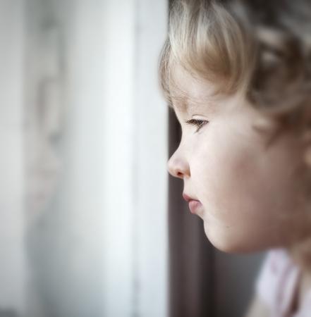 year profile: Sad little girl looking at window