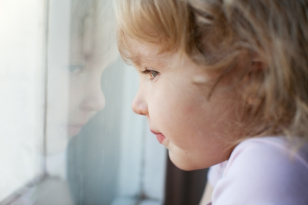 sadness: Sad little girl looking at window