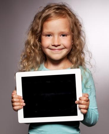Gl?ckliches Kind mit Tablet-Computer. Kid zeigt Tablet-Bildschirm