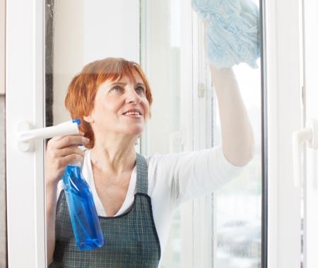 mature women only: Mature woman cleaning window. Female washing window