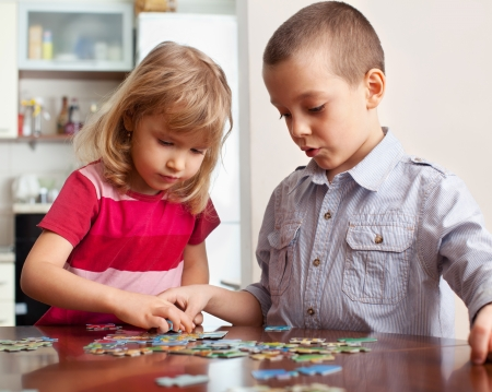 preschool children: Children, playing puzzles at home Stock Photo