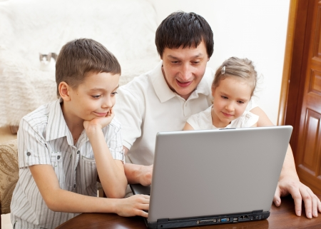 Happy family with laptop. Father with children play in the computer photo