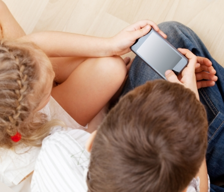 topdown: Children with smart phone. Boy and girl play smart phon Stock Photo