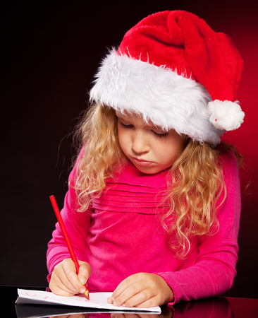 Child writing a letter to santa claus. Little girl